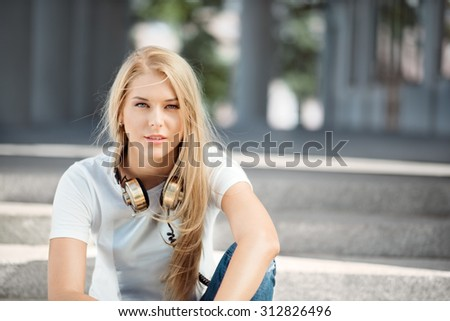 Beautiful young woman with vintage music headphones around her neck, sitting against urban city background and looking straight. - stock photo