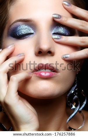 Beautiful young woman with vogue shining sparkle face makeup and closed eyes