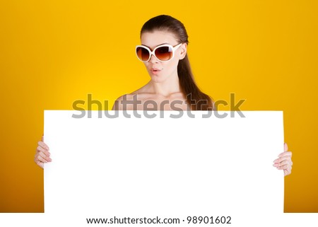 Beautiful young woman with white blank isolated on yellow background - stock photo