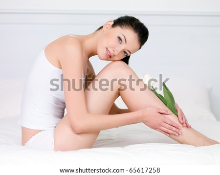 Beautiful young woman with white tulip on her attractive perfect legs - indoors