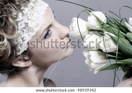 Beautiful young woman with white tulips over gray background - stock photo
