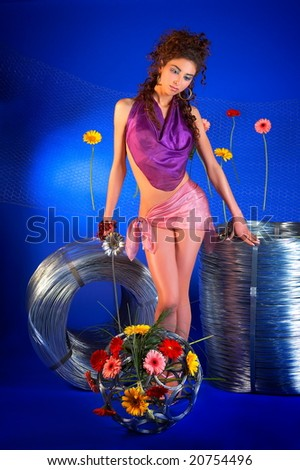 beautiful young woman with wire rolls and flowers