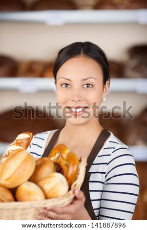 beautiful young woman working in bakery showing basket with bread loafs - stock photo