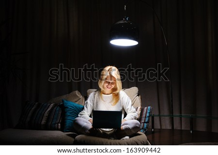 beautiful young woman working in the evening at a laptop sitting on the couch - stock photo