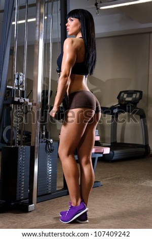 Beautiful young woman working out in fitness club - stock photo