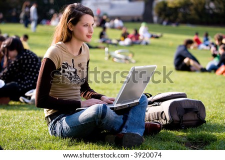 beautiful young woman working with her notebook is sitting outdoors - stock photo