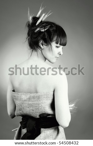 Beautiful young woman worth a back with wheat ear in her hair. Nature  concept. - stock photo