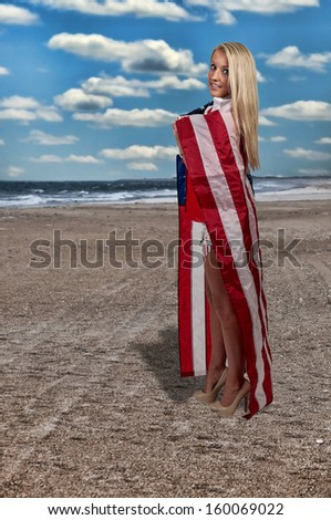 Beautiful young woman wrapped in a flag. - stock photo