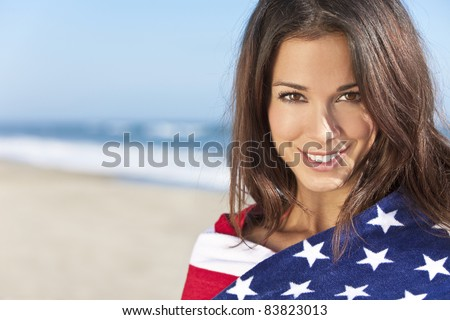 Beautiful young woman wrapped in American flag towel on a sunny beach - stock photo
