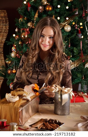 Beautiful young woman wrapping a christmas gift - stock photo