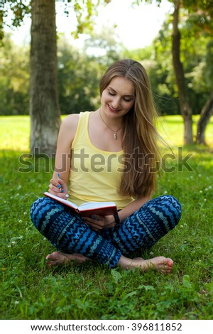 Beautiful young woman writes in diary in the park - stock photo