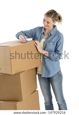 Beautiful young woman writing on cardboard boxes against white background