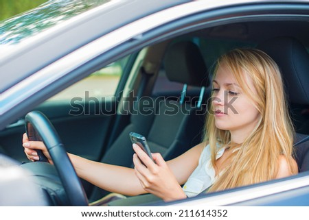 Beautiful young woman writing sms while driving car. - stock photo