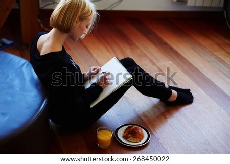 Beautiful young woman writing something in the note pad while sitting on the floor at living room, charming female studying doing homework at home, girl writes diary at her breakfast, flare light - stock photo