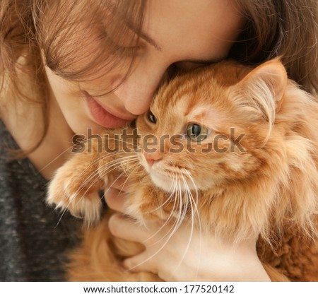 beautiful young woman 20 years with a fluffy red cat - stock photo