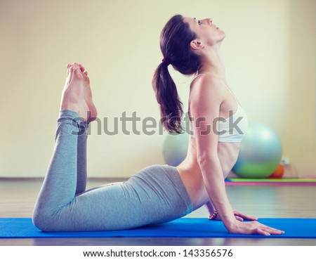 Beautiful young woman yoga workout in gym - stock photo