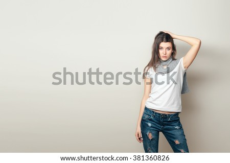 Beautiful young woman. Young girl. Girl in jeans and a gray scarf. Beauty portrait.  Girl portrait on a gray background. Ripped jeans. Toned image - stock photo