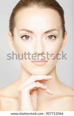 Beautiful young womans face with her hand resting on her chin in a beauty style pose - stock photo