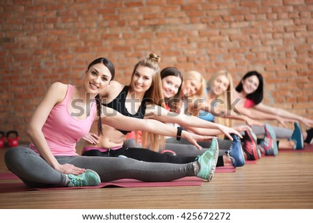 Beautiful young women are exercising in class - stock photo