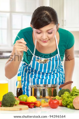 beautiful young women cooking and smell the food in the kitchen - stock photo
