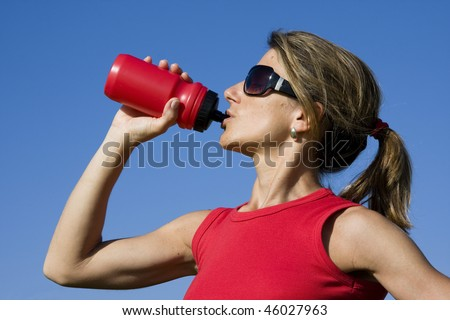 Beautiful young women drinking after exercise - stock photo