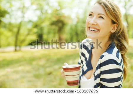 Beautiful young women drinking tea and relaxing after doing yoga class in nature. - stock photo