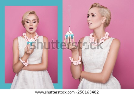 Beautiful young women holding small cake with colorful candle. Birthday, holiday. Studio portrait over pink and blue background - stock photo
