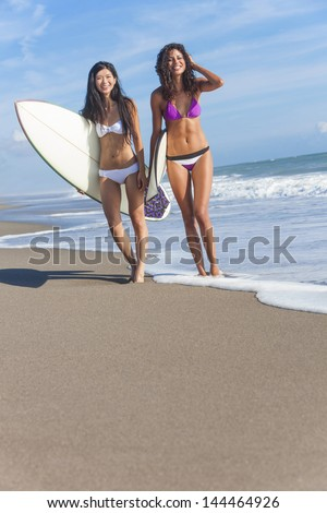 Beautiful young women surfer girls in bikinis with surfboards standing in the sea laughing on a sunny beach - stock photo