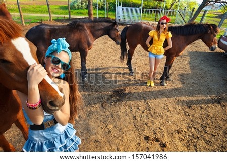 Beautiful young women wearing  with a horses outdoor. - stock photo