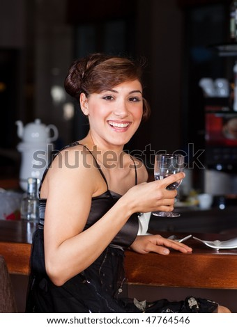 Beautiful young women with great smile and hairstyle sitting at a bar, drinking water. - stock photo