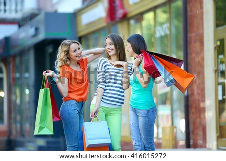 Beautiful young women with shopping bags on city street - stock photo
