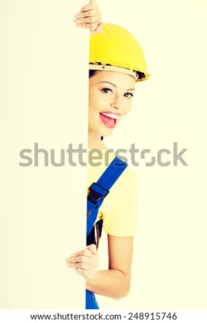 Beautiful young worker woman in protective clothes and helmet.