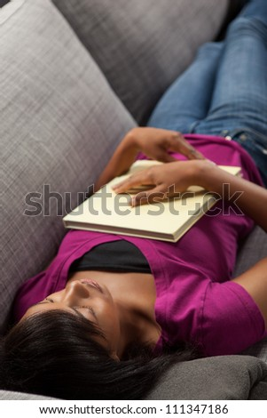 Beautiful youthful African American woman relaxing at home on grey couch wearing pink shirt. - stock photo