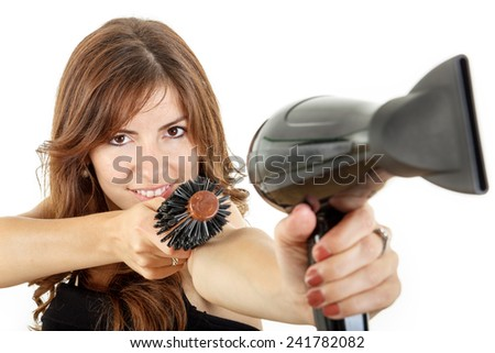 Beautifule female hairdresser using hairdryer and hairbrush pointing at camera smiling - stock photo