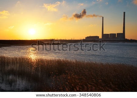 Beautifull landscape with thermal power plant, lake and sunset sky. - stock photo