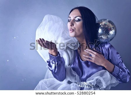 Beautifull woman stylised on club fairy blowing off from palm silver spangles. Fashion Photo. - stock photo