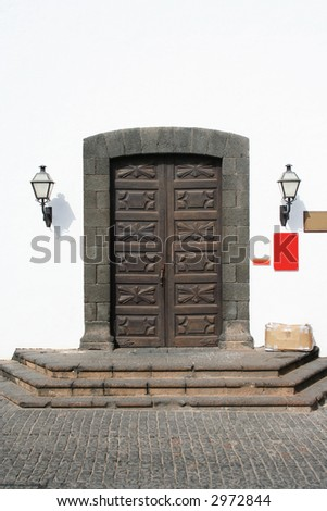 Beautifully carved wooden doors to a monastery, now a museum. Shaped lava rock surround and an old cardboard box of stuff on the doorstep! - stock photo