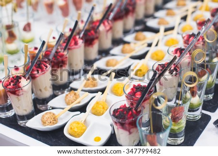 Beautifully decorated catering banquet prepared table with different food snacks and appetizers with sandwich, caviar, fresh fruits on corporate christmas birthday party event or wedding celebration  - stock photo