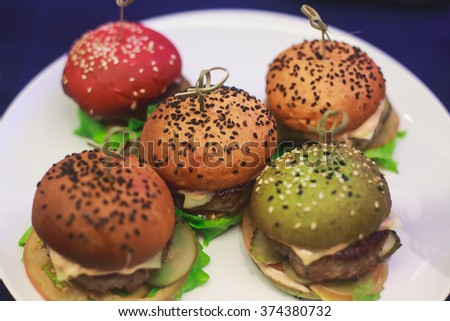 Beautifully decorated catering banquet table with different colored hamburgers burgers sandwiches on a plate on corporate christmas birthday party event or wedding celebration