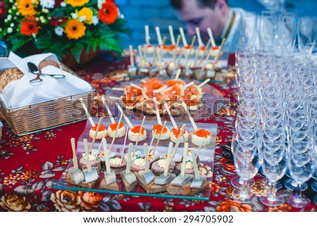 Beautifully decorated catering banquet table with different food snacks and appetizers with sandwich, caviar, fresh fruits on corporate party event or wedding celebration - stock photo