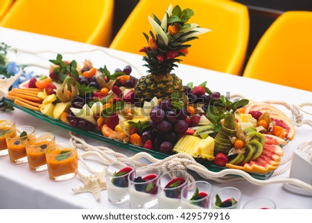 Beautifully decorated catering banquet table with different food snacks and appetizers with sandwich, caviar, fresh fruits on corporate christmas birthday kids party event or wedding celebration - stock photo
