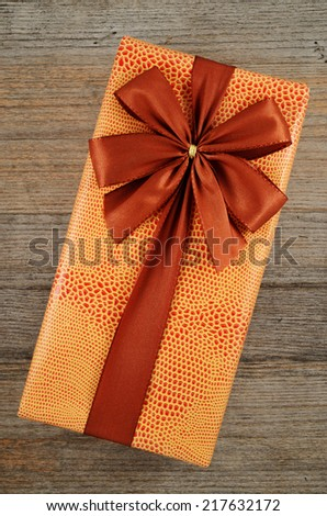 beautifully decorated gift box with bow on wooden background - stock photo