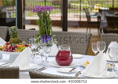 Beautifully decorated table in the restaurant. Fresh flowers and fruit. Selective soft focus