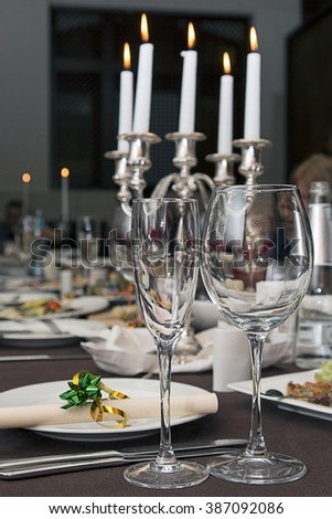 Beautifully decorated table in the restaurant. In the foreground of wine glasses - stock photo