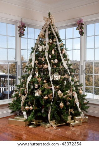 Beautifully decorated xmas tree in the corner of a large luxurious family room - stock photo