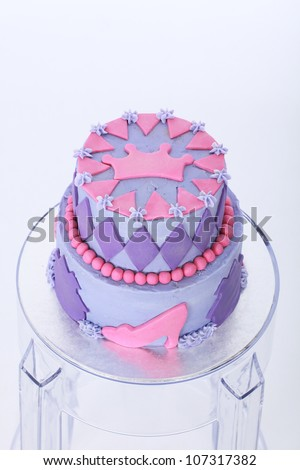 Beautifully designed and decorated two double tier princess themed birthday cake with purple and pink butter and fondant icing featuring beads shoes crown and diamonds on clear acrylic bar stool stand - stock photo