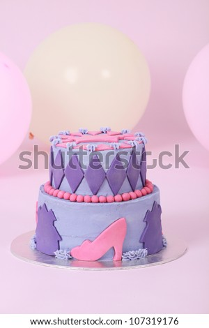 Beautifully designed and decorated two double tier princess themed birthday cake with purple and pink butter and fondant icing featuring beads shoes crown and diamonds on pink background with balloons - stock photo