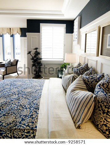 Beautifully designed bedroom interior with white and blue coloring and shutters - stock photo