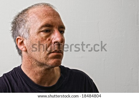 beautifully detailed real portrait of haggard and weathered looking adult white man staring blankly into space - stock photo