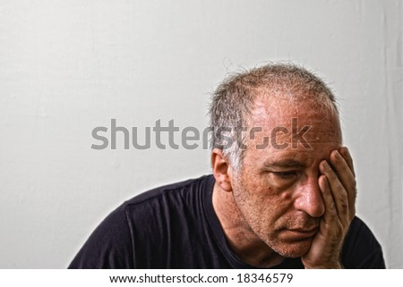 beautifully detailed real portrait of haggared looking adult white man holding his head as if having a headache or is in deep dispair - stock photo